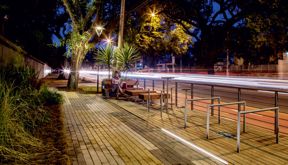 """QUE TAL SENTAR E CONVERSAR? Com 2 m de largura, a faixa de serviço junto à rua mescla às árvores bicicletário, postes de luz (Schréder do Brasil), lixeiras e mobiliário de jatobá certificado (mmcité). """"Ao oferecer formas de usar o local, evita-se que ele vire terra de ninguém. Por causa da ciclovia vizinha, alocamos o parklet numa parte da calçada"""", observa Felipe. (Foto: Zé Gabriel)"""